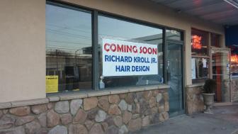 A sign promotes a new business in Black River Plaza--Richard Kroll Jr. Hair Design.