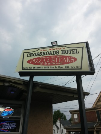 A large sign mounted on metal posts by the Crossroads Hotel pickup window was damaged when a car struck it Monday afternoon.