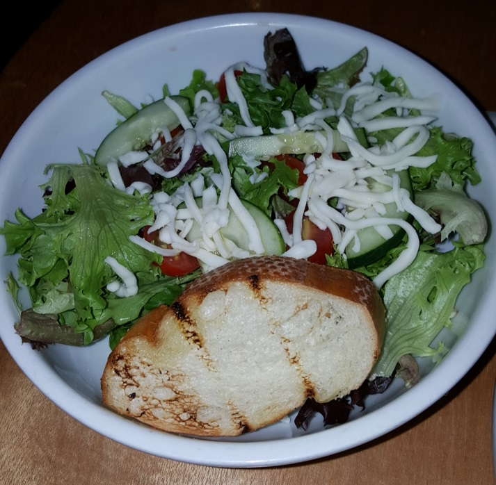 A house salad at Sagra features shredded cheese and a piece of toasted bread. It is served with a choice of dressing.