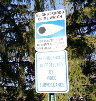 A neighborhood crime watch sign along Old Mill Road warns visitors that suspicious activity is reported to police and that the area is under video surveillance.