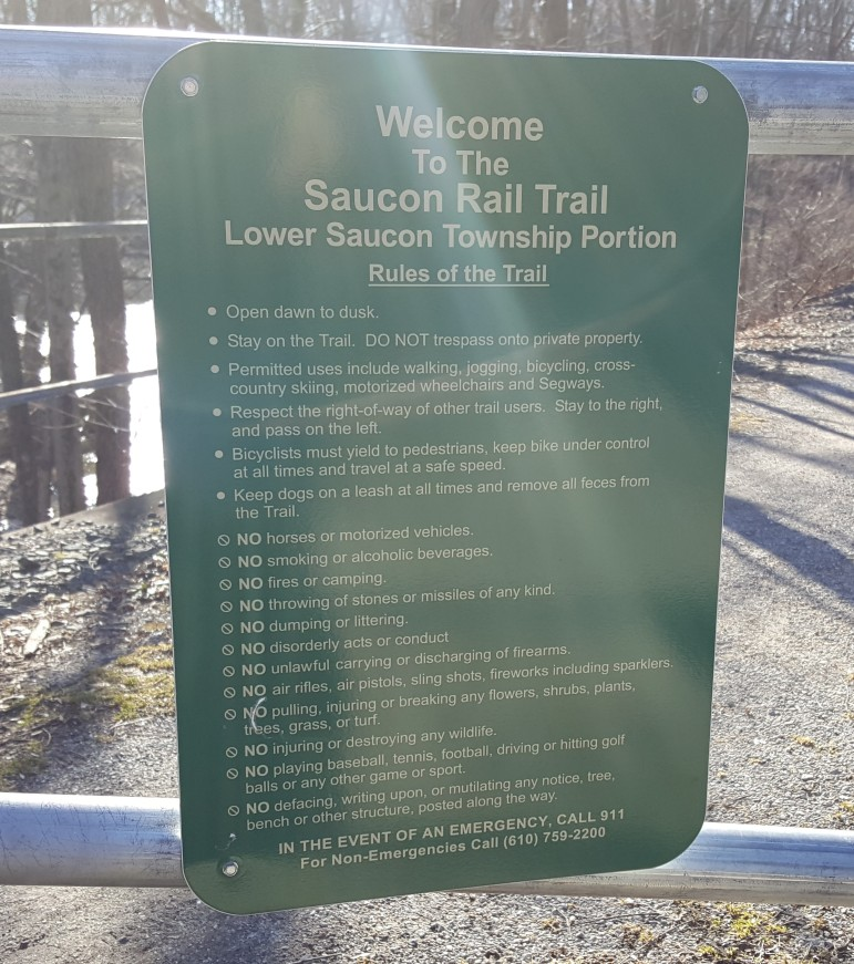 A sign enumerating the rules for trail users in Lower Saucon Township is affixed to the gate at the Old Mill Road trail crossing.