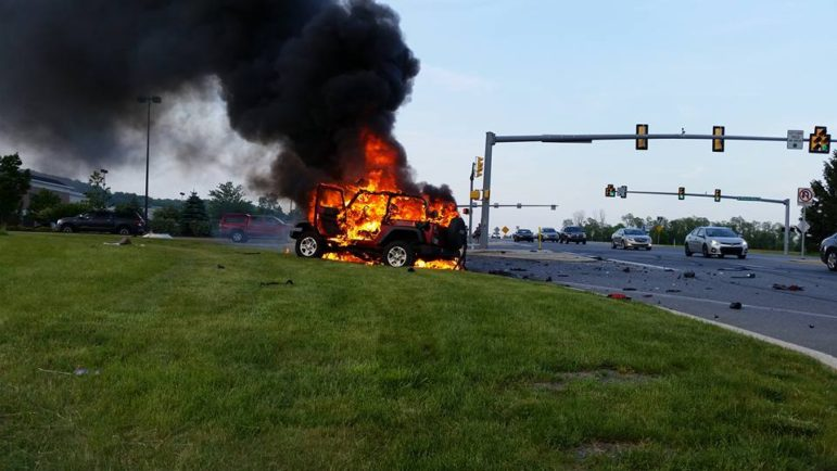 A Jeep burns near an entrance to the Promenade Shops at Saucon Valley in Upper Saucon Township following a violent accident on Center Valley Parkway Friday evening.