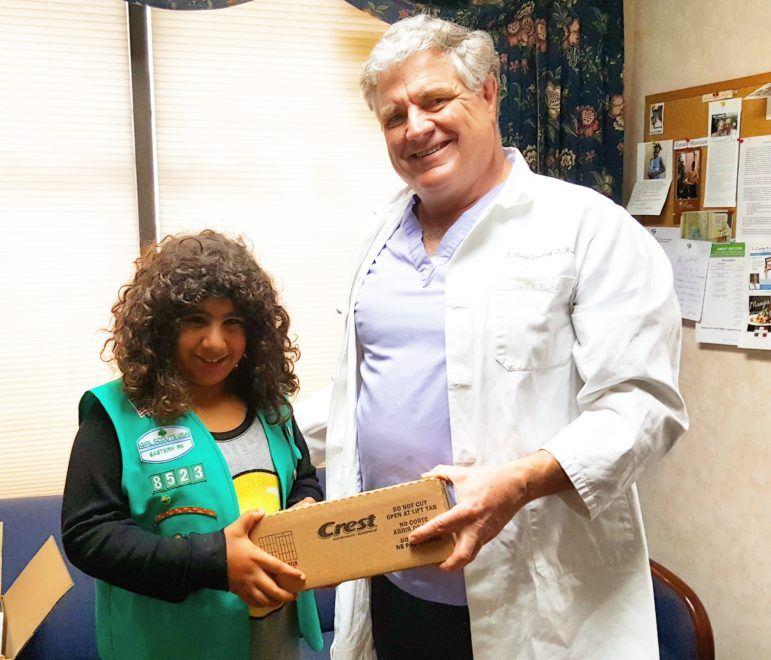 Dr. S. Clarke Woodruff, DDS, of Hellertown, presents Girl Scout Charisma Levens-Oyer with a box of Crest toothpaste and other oral hygiene items that will be donated to families in need.