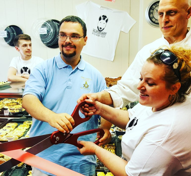 Hellertown-Lower Saucon Chamber of Commerce board chairman/borough council president Tom Rieger helps Hellertown Bakery owners Leiane McCarty and Joe Ciamprone cut the ribbon at their store Saturday morning. The bakery opened  for business in early April.