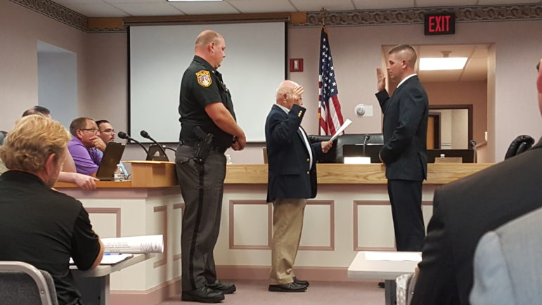 Hellertown Mayor Richard Fluck administers the oath to Ofc. Christopher Pfancook, who was promoted to full-time in the Hellertown Police Department.