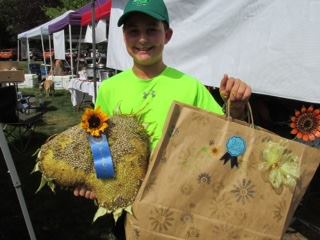 First place youth category winner James Hall with his prize-winning sunflower seed head