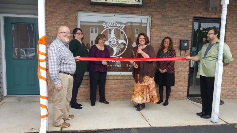 Kindred Spirits Books & Gifts owner June Rose (center) prepares to cut the ribbon on an extension of her business--Sacred Space--in Hellertown Saturday. Looking on are Hellertown-Lower Saucon Chamber's Mark Albright, and the Sacred Sisters: