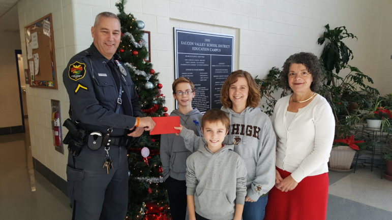 Ofc. Chuck Werkheiser of the Lower Saucon Township Police Department presents a gift to the Roseman-Gilly family at Saucon Valley Middle School. Pictured at right is middle school principal Pamela Bernardo.