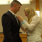 Ofc. Giorgi's wife Morgen pins his badge on his lapel at a swearing in ceremony at Lower Saucon Town Hall Thursday.